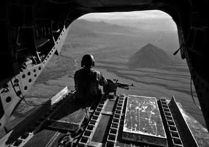 An American Chinook helicopter crewman looks out over the border region between Afghanistan and Pakistan in 2008, where the heaviest fighting occurred at that time. NATO forces have little presence in areas between major bases. Photo: Graham Lavery