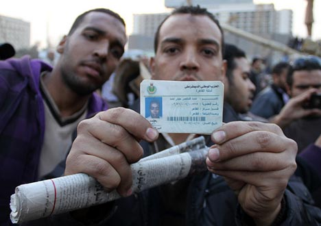 Protesters in Tahrir Square, Cairo, with identification taken from a pro-Mubarak rioter which shows that person to be a member of security forces. Feb. 2, 2011. Photo: omarroberthamilton/Flickr