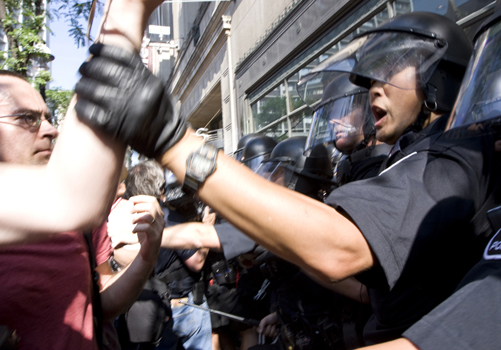An anti-riot policeman grabs a protester by the wrist during the anti-poverty protest on Friday in Toronto. Up to 10,000 protesters are expected to gather at Queen's Park today at 1 p.m. EST. Photo: Kristen Hanson.