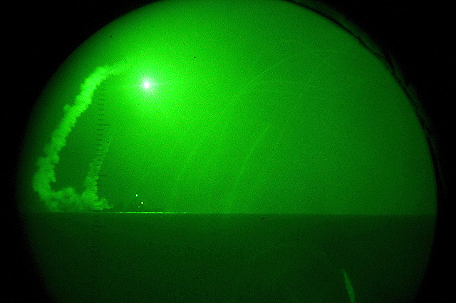 Seen through night-vision lenses aboard amphibious transport dock USS Ponce, the guided missile destroyer USS Barry fires Tomahawk cruise missiles in support of Operation Odyssey Dawn against Libya. Photo: U.S. Navy/Nathanael Miller
