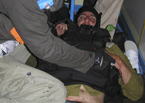 On board the Mavi Marmara as it was under attack: An Israeli commando soldier is panicked, but being treated for injuries after being captured by peace activists. Photo: Kevin Neish.