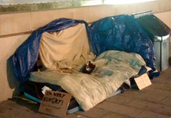 An elaborate outdoor sleeping encampment on a Toronto sidewalk. A cardboards sig